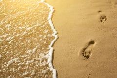 Spuren der Füße im Sand auf dem Strand Stockfotos