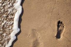 Spuren der Füße im Sand auf dem Strand Stockfoto