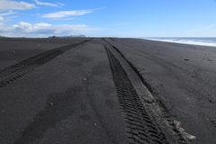 Spuren des Autos auf schwarzem Sand Stockbild