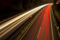 Spuren des roten und weißen Lichtes mit einer Höchstgeschwindigkeit unterzeichnen herein die Mitte nachts Geschwindigkeitsbeschrä Lizenzfreie Stockbilder