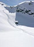 Spuren im alpinen frischen Schnee Stockbilder