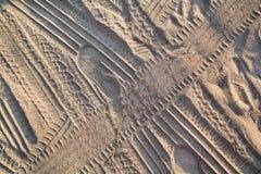 Spuren im Sand Teil Drucke und Bahnen des Reifens, Fuß, Füße, Sonnenseepantoffel im Strandsand lizenzfreie stockfotografie