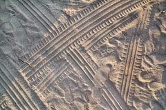 Spuren im Sand Teil Drucke und Bahnen des Reifens, Fu?, F??e, Sonnenseepantoffel im Strandsand lizenzfreies stockbild