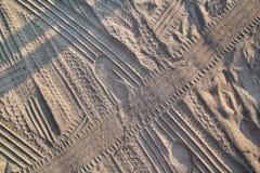 Spuren im Sand Teil Drucke und Bahnen des Reifens, Fu?, F??e, Sonnenseepantoffel im Strandsand lizenzfreie stockfotografie