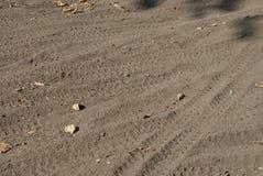 Spuren von Fahrradreifen auf grauem braunem Sand stockfotos