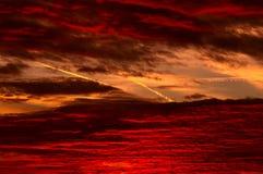 Spuren von Flugzeugen im Himmel während des Sonnenaufgangs. Stockbilder