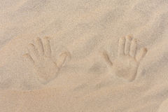 Spuren von zwei Kind-` s Hand auf goldenem Sand Stockfotos