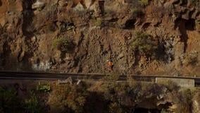 Spurhaltung der Videoaufnahme eines männlichen Radfahrers, der oben eine Gebirgsstraße klettert Bemannen Sie Radfahrentraining au stock video