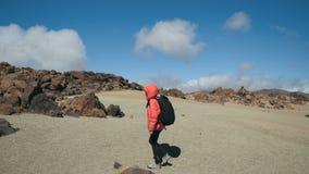 Spurhaltung des Schusses einer jungen Frau mit dem Rucksack, der entlang dem vulkanischen Sand unter Lavafelsen in einem enormen  stock video footage