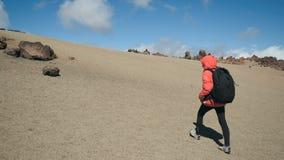 Spurhaltung des Schusses einer jungen Frau mit dem Rucksack, der entlang dem vulkanischen Sand unter Lavafelsen in einem enormen  stock video