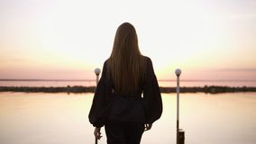 Spurhaltung von Rückseitengesamtlänge einer großen, langhaarigen Frau, die in schwarze Kleidung durch den Pier geht Kleidungsmode stock footage