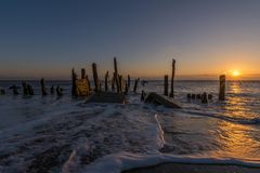 Spurn Point old wooden groynes and beach sea defences. Spurn Point beach photography at sunrise around old wooden sea defences and groynes at first light Royalty Free Stock Photo