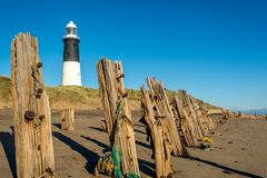 Spurn Point lighthouse and old wooden beach sea defences. Spurn Point beach photography at low tide around wooden sea defences and old lighthouse Royalty Free Stock Photos