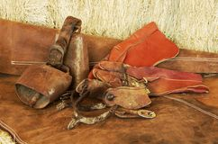 Spurs, gloves and bells. Spurs, gloves, bells and chaps resting on hay bales stock photography