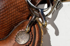 Spurs. A set of spurs on a saddle with a concho in the background stock photography