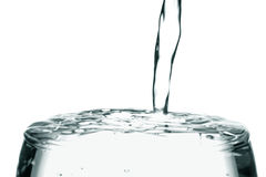 Spurt of pure water. Falling into a glass royalty free stock photo