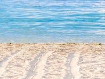 Spurweiten auf dem Strand und undeutlichen blauen dem Seehintergrund Lizenzfreie Stockfotos