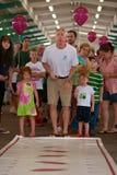 Sputi dell'uomo nel concorso dell'emissione del seme dell'anguria al mercato degli agricoltori Fotografia Stock Libera da Diritti