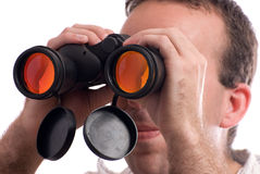 Spy. Closeup view of a man spying with a set of binoculars, isolated against a white background Royalty Free Stock Photos