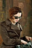 The spy. A young stylish woman in a trench coat and sunglasses Stock Photos