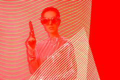 Spy Agent with Gun in Red and Yellow Light Painting Backdrop. Tough steampunk woman with pistol Stock Photos