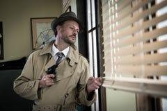Spy agent peeking from a window Stock Photo
