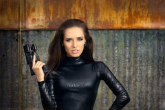 Spy Agent Woman in Black Leather Suit Holding Gun. Portrait of a cool super heroine in action Royalty Free Stock Photography