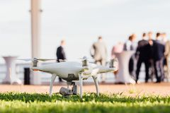 Spy drone, helicopter, quadrupter Dron before take-off on grass, against the backdrop of people. Spy drone, helicopter, quadrupter before take-off on green stock images