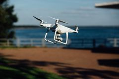 Spy drone, helicopter, quadrupter flies through the territory of the hotel cafe. A high-definition camera shoots photos and videos. White quad copter flying royalty free stock photography