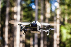 Spy drone in the wild. A small spy quad copter scout drone flying through the trees in a forest stock image
