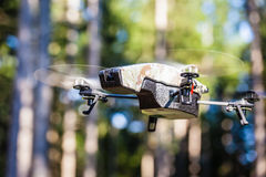 Spy drone in the wilderness. A small spy quad copter scout drone flying through the trees in a forest stock images