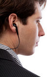 Spy with earphone. A closeup of a handsome spy with a tap in his ear stock image