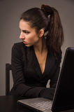 Spy girl in a black with laptop Stock Photography