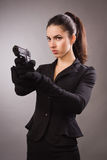 Spy girl in a black shoots a gun Royalty Free Stock Photo