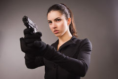 Spy girl in a black shoots a gun Royalty Free Stock Photography