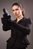 Spy girl in a black shoots a gun. Spy girl in a black suit shoots a gun Royalty Free Stock Images