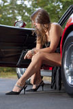 Spy girl with gun. Exiting car Stock Image