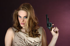 Spy girl with gun pointing up on red background. Head and shoulders portrait of female spy agent holding black gun on red background Stock Image