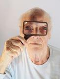 Spy Glass. The senior spys through the glass, to create a weird portrait Stock Photography