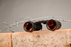 Spy glass atop of a wall. A concept on migratory issues in current politics royalty free stock photos