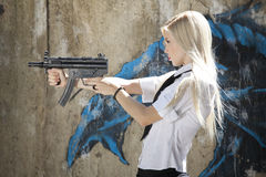Spy with gun aiming. Young female spy in white blouse and tie holding a automatic machine gun Royalty Free Stock Photos