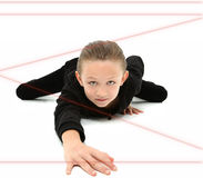 Spy Kid. Adorable 7 year old girl dressed as spy crawling through red laser beams over white background Royalty Free Stock Images