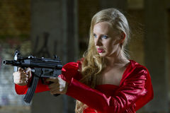 Spy with machine gun. Sexy female spy in red dress and raincoat holding machine gun - outdoor Stock Images