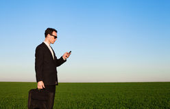 Spy with mobile. Businessman with smartphone in green field Stock Image