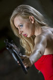 Spy in red dress and gun. Sexy spy in red dress and machine gun in old fabric Stock Image