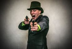 The spy. Secret service. Detecive agent. The spy. Secret service. Angry Detecive agent holds pistol gun in his hands aiming and attack. Retro wicked gangster Stock Image