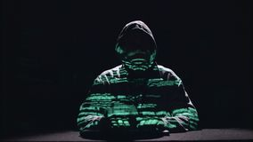 Spy is typing virus patches on the keyboard for hacking. Black background. Silhouette. Spy sits in a dark room at the table and prints on the keyboard a virus stock video