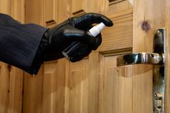 Spy sprays a poisonous substance on the door handle, sabotage work royalty free stock photo