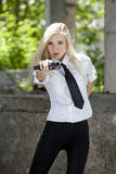 Spy woman with gun. Spy woman in white blouse and tie, aiming with a handgun Royalty Free Stock Photography