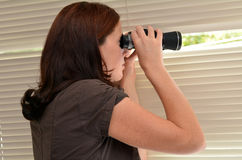 Spy Woman. Young woman (age 25-30 ) searching with binoculars and  looks out through blinds. Concept photo of curious, spy, nosy woman Royalty Free Stock Photos